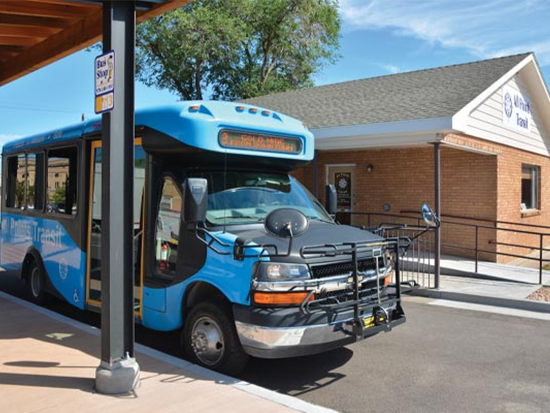 All Points Transit blue bus sits at pick up location