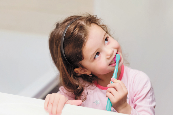 Children brushing teeth with fluoride water