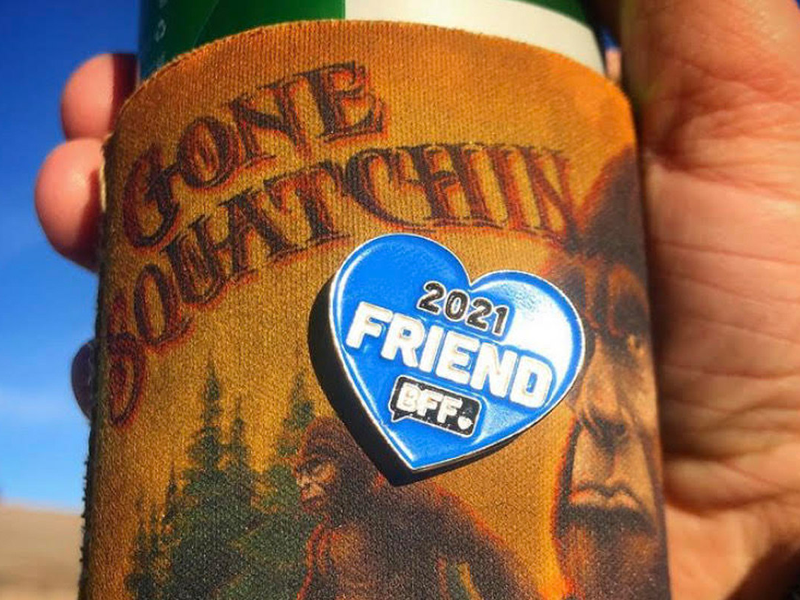 hand holding sasquatch koozie with BFF pin