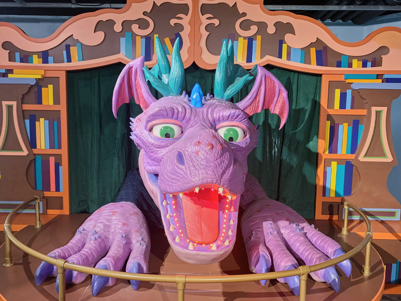purple dragon's head bursting through stage curtains