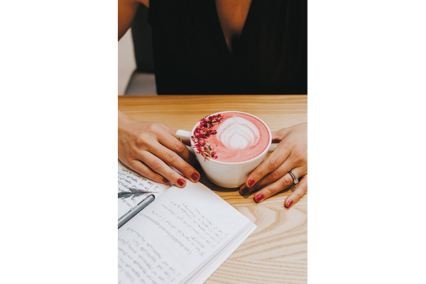 A women holding a cup of Hibiscus Rose Latte