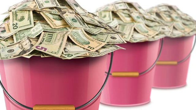 Three pink buckets almost overflowing with cash, of multiple different bills