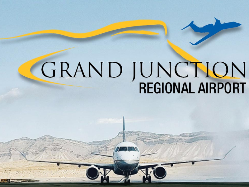 The Grand Junction Regional Airport logo overlaid on an image of an airplane coming down the runway
