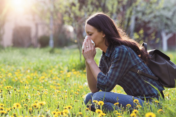 Allergy sufferer blowing nose outside experiencing more symptoms from climate change