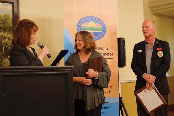 Linda Sedeghi, owner of Casino San Clemente, accepts a plaque from Pat Bates.