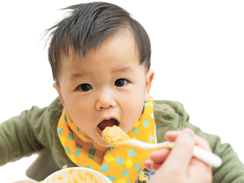 Baby with bib on being spoon fed bowl of healthy homemade baby food