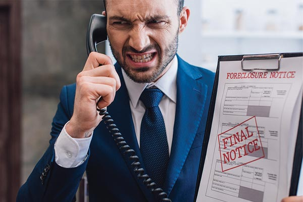 "Angry man in business suit on phone holds clipboard with stamp ""final notice"""