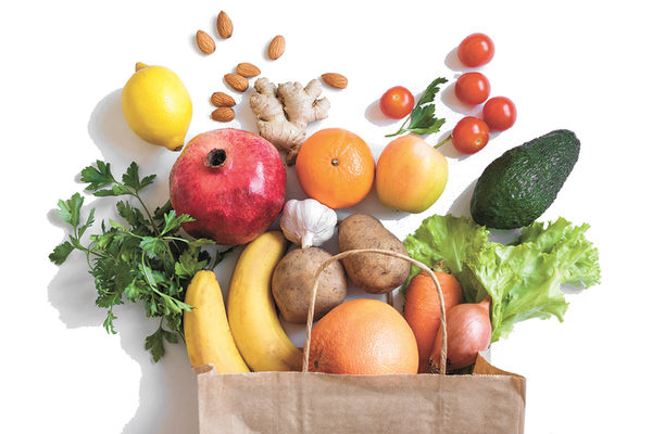 Brown paper grocery bag full of fresh produce fruits and vegetables