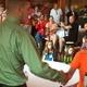 Nick Pearson congratulates age group winner Joseph Balboni at the Tewksbury Memorial Day 5K Fun Run.