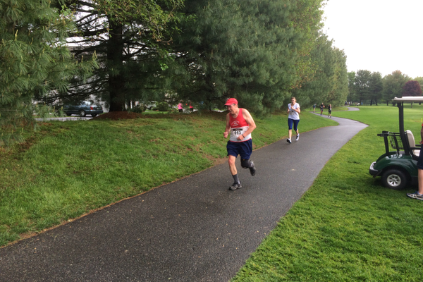 Ken Deaky, the 60-69 age group winner, pushes through to the finish line at the Tewksbury Memorial Day 5K Fun Run.