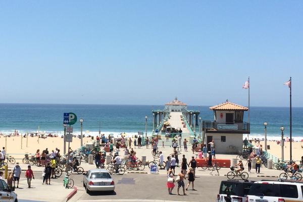 Authorities closed the MB Pier after a fisherman's effort to land a great white shark led to a swimmer being bitten; news crews crawled the pier area and beach.