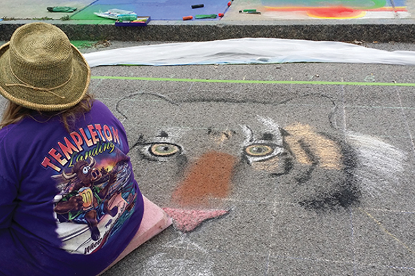 Jeannette Pikturna draws a tiger at the Sweet Chalk Festival.
